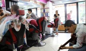 Canlı müzik eşliğinde müşterilerini tıraş ediyor